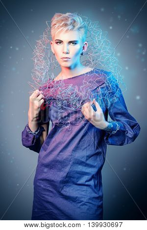 Close-up portrait of a fashion model performing designer collection with the use of metal wire. Avant-garde style. Futurism. Studio shot.