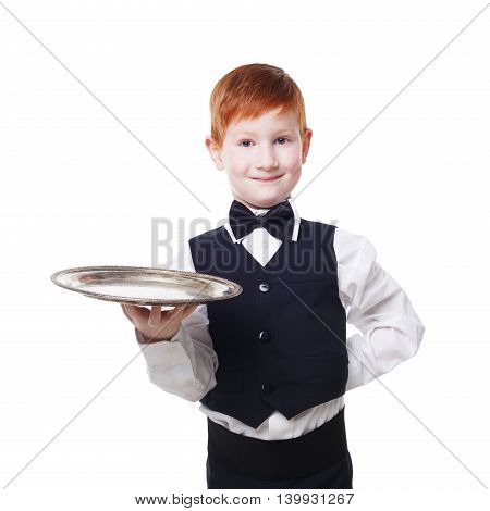 Little waiter stands with empty tray serving. Smiling redhead child boy in suit plays restaurant servant at blue background