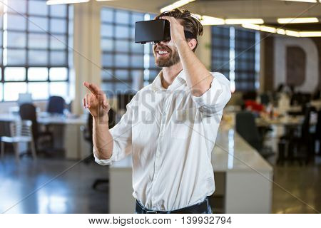 Businessman smiling while using virtual reality simulator in office