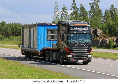 PAIMIO, FINLAND - JULY 1, 2016: Scania R500 truck transports portable cabin along motorway at summer. Portable cabins are often used as as temporary offices on building sites.