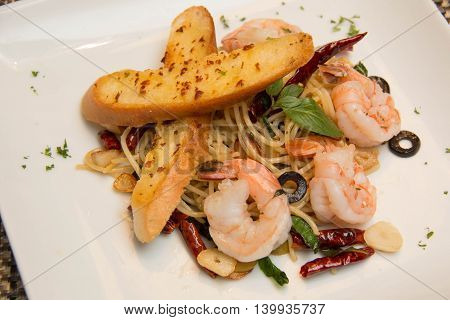 Stir-fried spicy spaghetti with shrimp and garlic bread