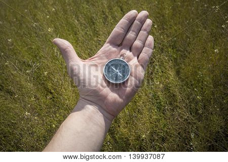 compass in hand of man to focus on areas in nature, in the mountains or on the plains