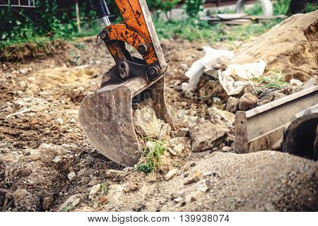 Industrial Backhoe Excavator With Close-up Of Metal Bucket Moving Earth At Construction Site