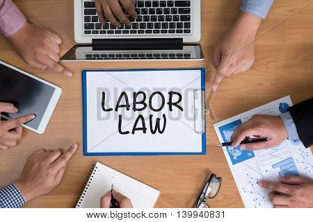 LABOR LAW Business team hands at work with financial reports and a laptop top view poster