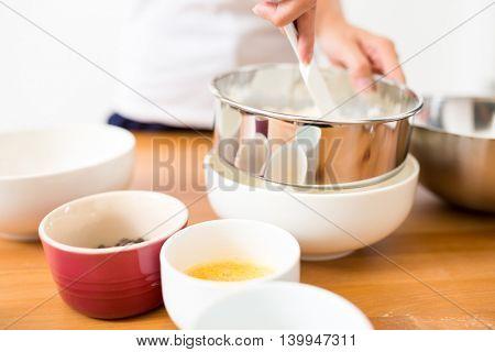 Woman sifting flour through a sieve in a bowl