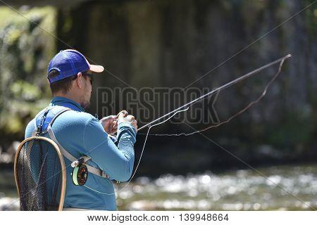 Fly-fisherman preparing fishing rod