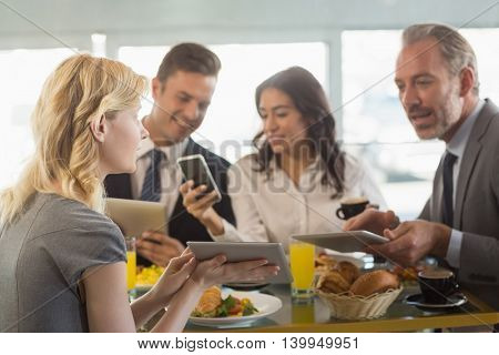 Business people using digital tablet and mobile phone while having meal in restaurant