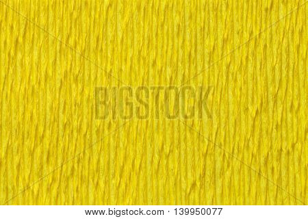 Textural yellow background of wavy corrugated paper close-up. Structural crepe cardboard macro shooting.