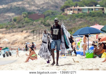 SANTA MARGHERITA DI PULA ITALY - JULY 05 2016: Black man selling clothes in Santa Margherita di Pula beach in Sardinia Italy