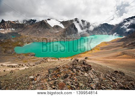 Picturesque turquoise mountain lake Ala-Kul. Alakol lake with cloudy sky. Tien Shan. Kyrgyzstan. Kirghizstan.
