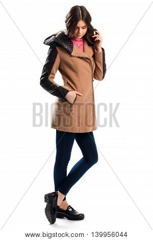 Woman in short beige coat. Skinny pants and shoes. Comfortable apparel of soft fabrics. Combination of fleece and leather.