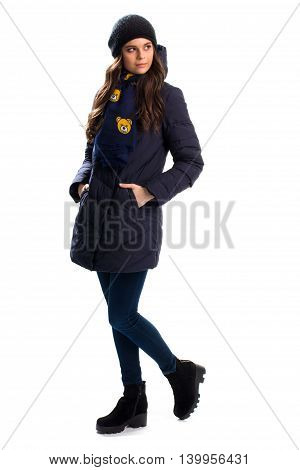 Woman wears navy down jacket. Cap and scarf with print. Warm boots and outerwear. Trendy winter clothes.