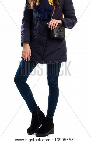 Girl wears navy down jacket. Boots and bag with strap. Winter outfit with leather handbag. Outerwear and warm shoes.