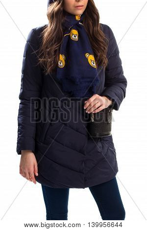 Young woman in down jacket. Navy scarf with bear pattern. Winter outfit and classic handbag. Outerwear of polyester.