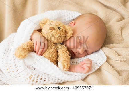 Infant sleeping together with teddy bear wrapped in blanket