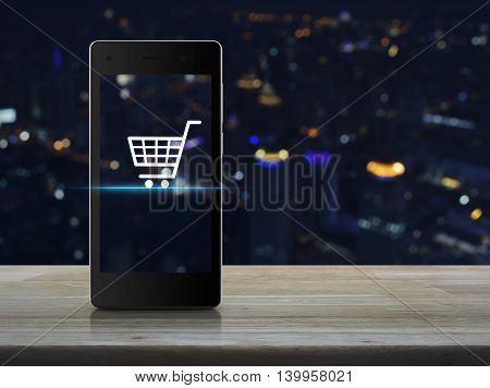 Shopping cart Icon on modern smart phone screen on wooden table over blur light city tower Shopping online concept