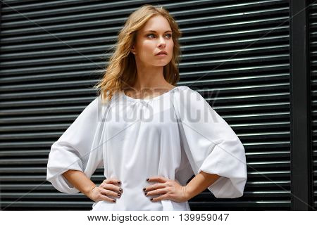 Portrait of blond woman in half-growth with hands akimbo on black wall background