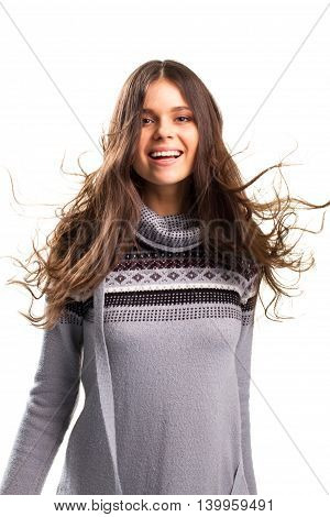 Lady with flying hair. Woman in gray pullover smiling. Capture the moment of joy. Ease and energy.