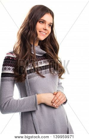 Young lady is smiling. Small pattern on pullover. Modest gesture and kind smile. Welcome to my home.