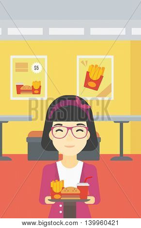 An asian woman holding tray full of junk food on a cafe background. Smiling woman in fast food restaurant. Woman having lunch in fast food restaurant. Vector flat design illustration. Vertical layout.