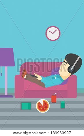 An asian man with belly relaxing on a sofa with many gadgets. Man lying on a sofa surrounded by gadgets. Man using gadgets at home. Vector flat design illustration. Vertical layout.