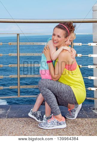 Happy Mother And Child In Fitness Outfit Hugging On Embankment