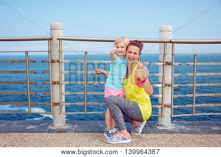 Happy Fitness Mother And Child On Embankment Showing Thumbs Up