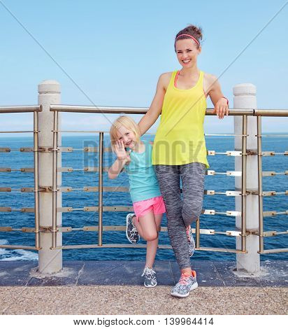 Fitness Mother And Child Standing On Embankment And Handwaving