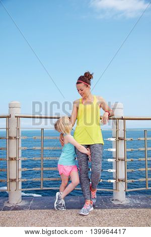Happy Mother And Child In Fitness Outfit Standing On Embankment