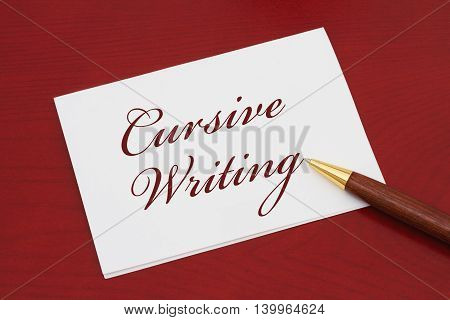 Learning how to write cursive White Greeting card with text Cursive Writing on a red wood background