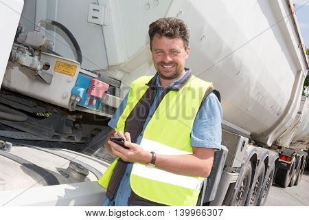 Real Construction Worker Using Mobile Telephone Beside Truck