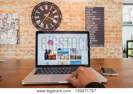 CHIANG MAI THAILAND - JUL 18 2016: A man using macbook laptop for instagram web application. Instagram is largest and most popular photograph social networking.