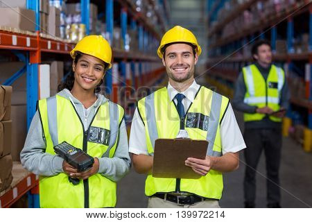 Smiling worker wearing yellow safety vest looking at camera in warehouse