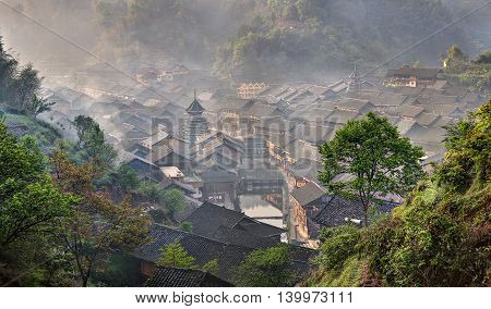 Ancient mountain village of Dong ethnic minority in southwest China the morning mist spring, Zhaoxing Dong Village Guizhou Province China. poster