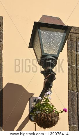 Electric street lamp on wall of building in Funchal Madeira Portugal