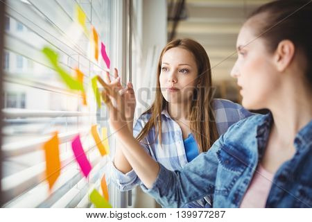 Young businesswoman discussing with colleague while looking at adhesive notes in creative office
