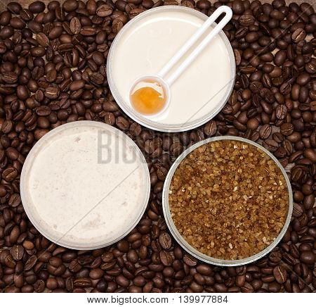 Cellulite busting products. Anti-cellulite cosmetics with caffeine. Jar of cream with spoon of coffee essential oil, coarse sea salt and natural body scrub surrounded by coffee beans