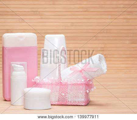 Cosmetics for babies. Different cosmetic products for baby skin care with cute wicker basket and small white towel on wooden surface. Copy space