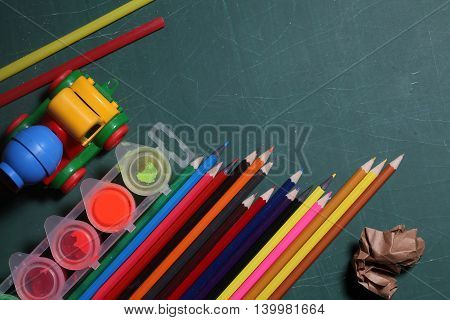 many colorful stationary of pencils for drawing art different colors laying on green school blackboard or desk with plastic car toy paint and paper copy space