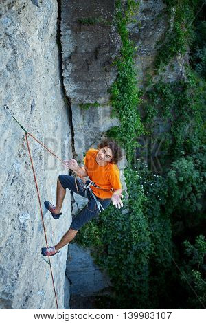 male rock climber. rock climber climbs on a rocky wall. man resting hanging on a rope