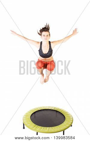 Closeup of a sportive woman bouncing on a trampoline - isolated on white.