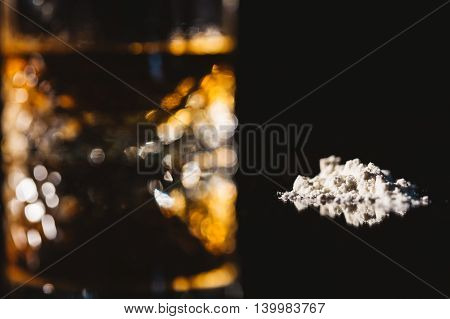 Blurred pose of a glass of alcohol and drugs. Focus on the drugs