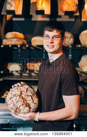Male baker or salesman in a bakery selling fresh bread and bakery products