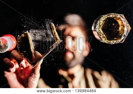 Blurred pose of a man holding razor blade for preparing a line of cocaine .Focus on the cocaine