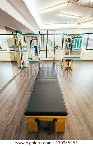 Pilates room having the equipment ready for clients. Focus on trapeze table.
