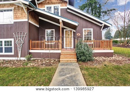 Two Level House Exterior With Wooden Pannel Trim And Porch