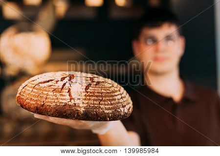Shopkeepers in a bakery presenting round bread with wheat ears