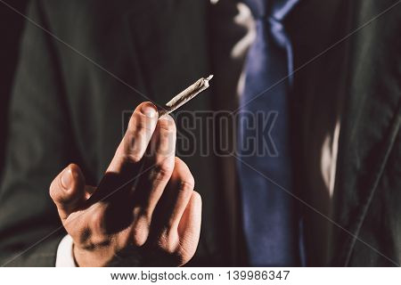 Business man's hand holding a joint in his hand