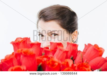 Mysterious woman hiding behind red roses - isolated on white