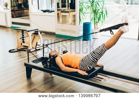Woman stretching in a pilates reformer close-up